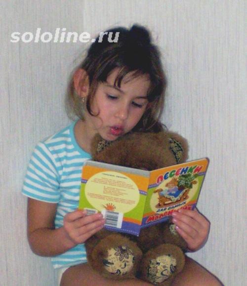 ребенок читает игрушечному медведю