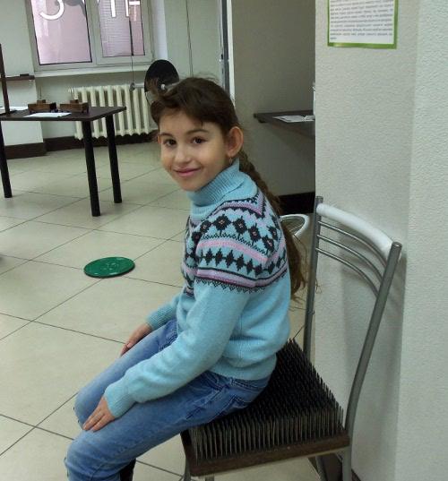 ребенок сидит на стуле с гвоздями