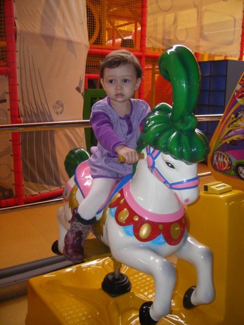 девочка на игрушечной лошадке