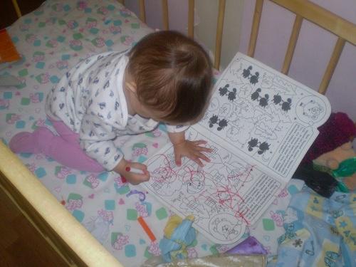 рисует в кроватке